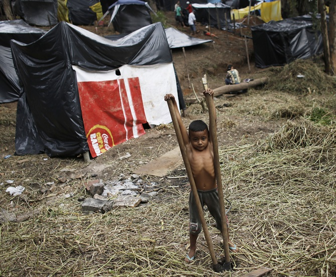 The son of a member of the Brazil's Homeless Workers' Movement (MTST) plays   with hoes at the 'People's World Cup' camp