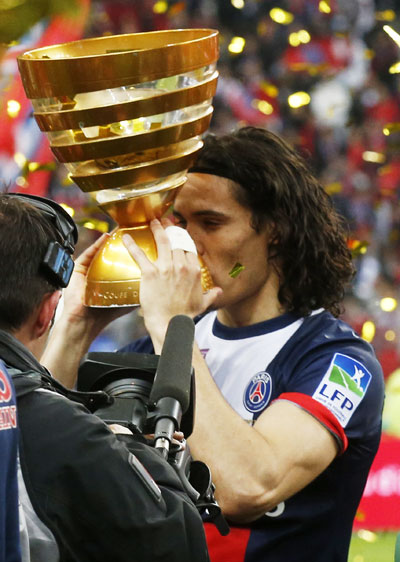 Paris St Germain's Edinson Cavani kisses the trophy after defeating   Olympique Lyon in the French League Cup final at the Stade de France stadium in Saint-Denis