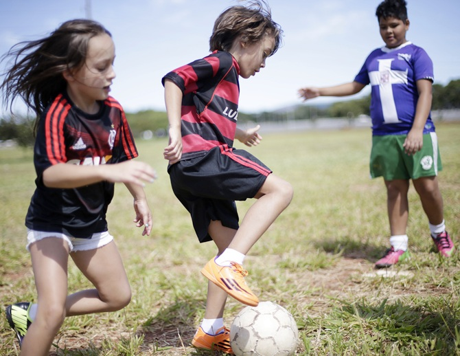 Children play a Sunday 'pelada' soccer match in front of the Mane Garrincha Stadium in Brasilia, a World Cup host city