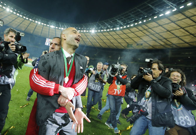 Bayern Munich's coach Pep Guardiola is carried by Franck Ribery as they celebrate winning their German Cup