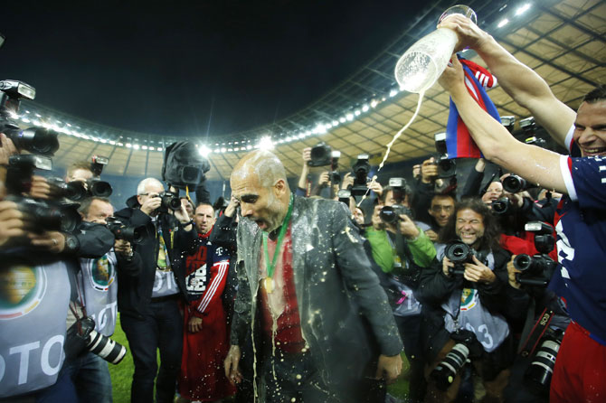 Bayern Munich's Claudio Pizarro (right) showers with beer coach Pep Guardiola after their German Cup