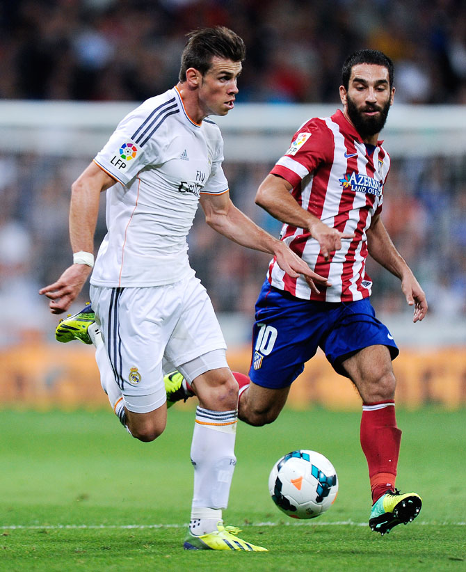 Gareth Bale of Real Madrid duels for the ball with Arda Turan of Atletico de Madrid