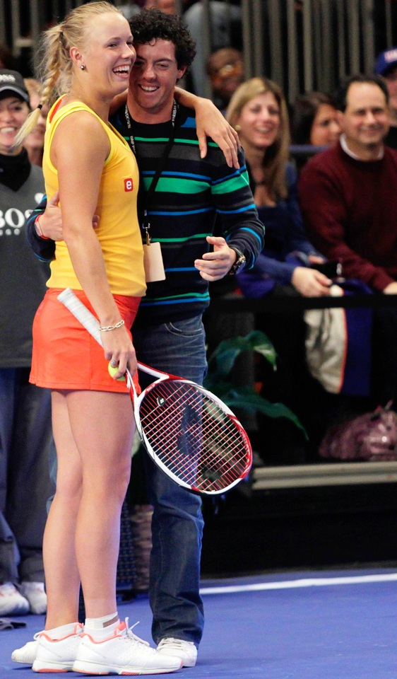 Golfer Rory McIlroy of Northern Ireland joins Caroline Wozniacki of Denmark on the court