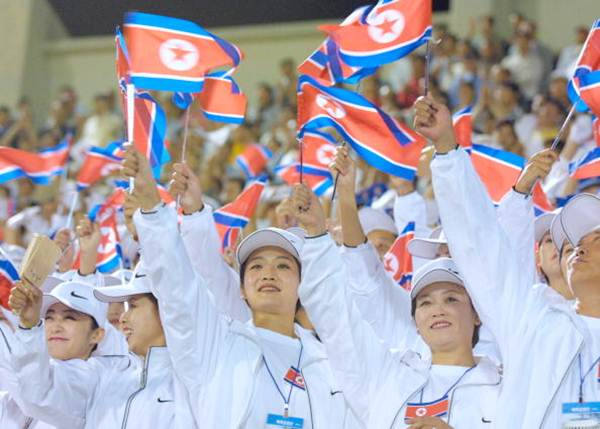 North Korean women wave their country's flags during a soccer