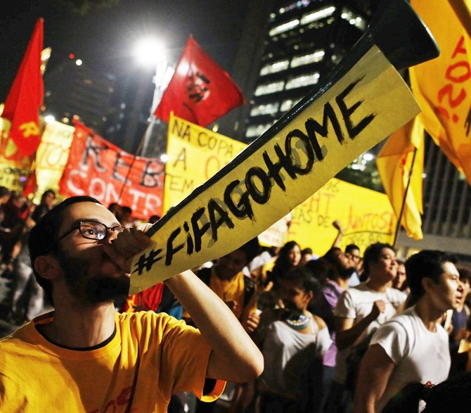 A demonstrator blows a horn during a protest against the 2014 World Cup, in Sao Paulo