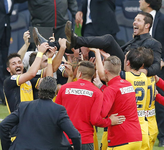 Atletico Madrid's players pick up their coach Diego Pablo Simeone after the team won the La Liga title