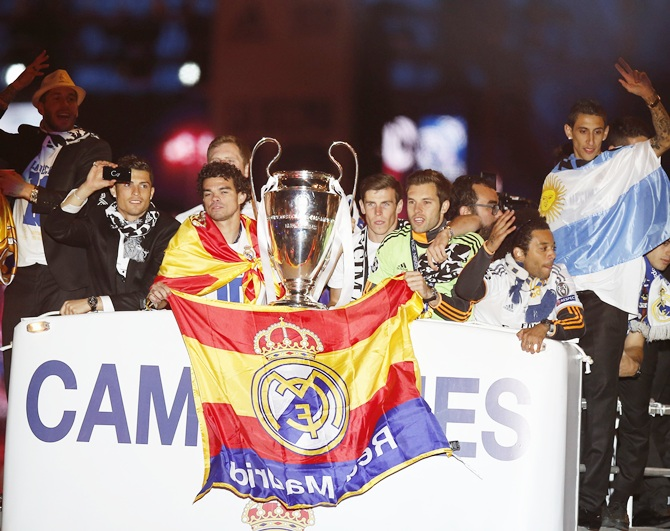 Real Madrid players celebrate on top of an open bus as they arrive at the Cibeles square after winning their Champions League final