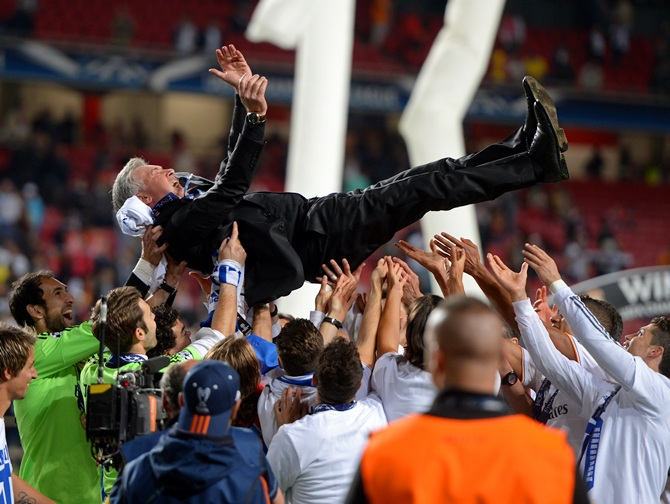 Head Coach, Carlo Ancelotti of Real Madrid is lifted in celebration by his players