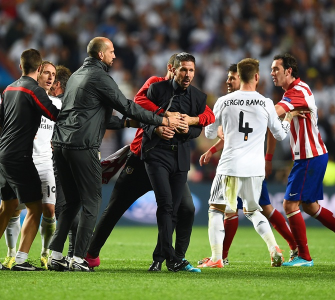 Diego Simeone, Coach of Club Atletico de Madrid is restrained as he clashes with Sergio Ramos of Real Madrid