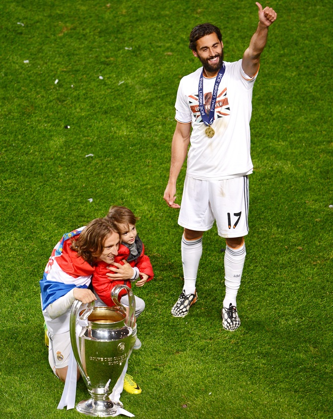 Alvaro Arbeloa of Real Madrid gives the thumbs up as Luka Modric of Real Madrid poses with the Champions League trophy