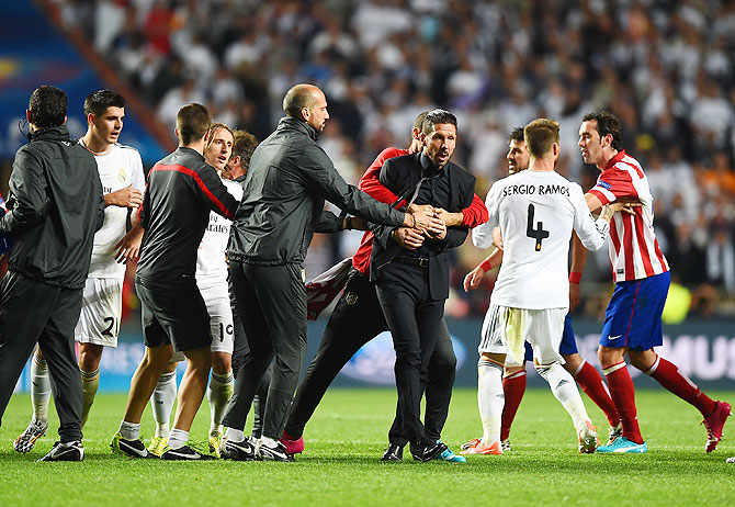 Diego Simeone, Coach of Club Atletico de Madrid is restrained as he clashes with Sergio Ramos of Real Madrid during the UEFA Champions League Final at Estadio da Luz in Lisbon on Saturday