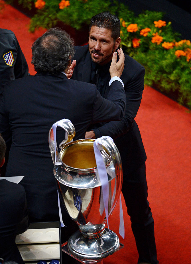 UEFA President Michel Platini presents Diego Simeone, coach of Club Atletico de Madrid with his runners up medal after the UEFA Champions League final on Saturday