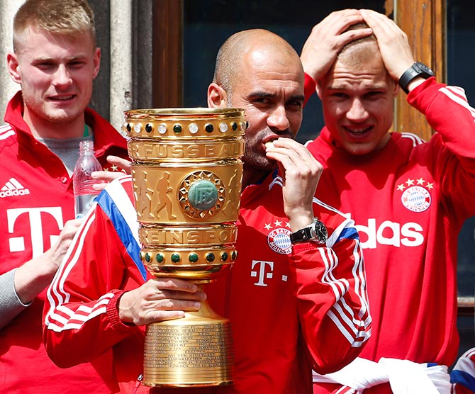 Bayern Munich's coach Pep Guardiola holds the German Cup trophy