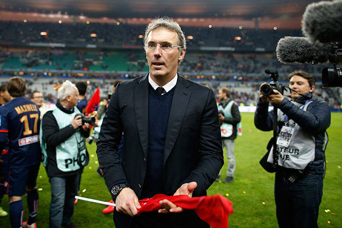 Paris St Germain's coach Laurent Blanc looks on while he celebrates defeating Olympique Lyon in the French League Cup final