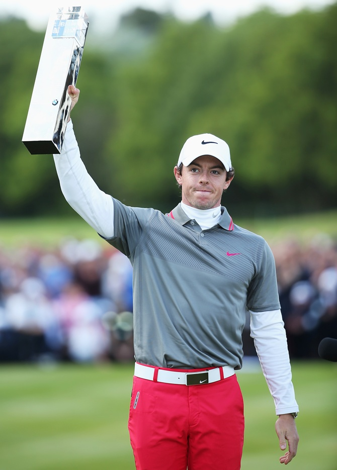 Rory McIlroy of Northern Ireland celebrates victory as he poses with the trophy