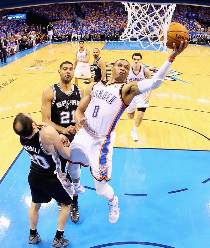 Russell Westbrook of the Oklahoma City Thunder drives to the basket against Manu Ginobiliof the San Antonio Spurs