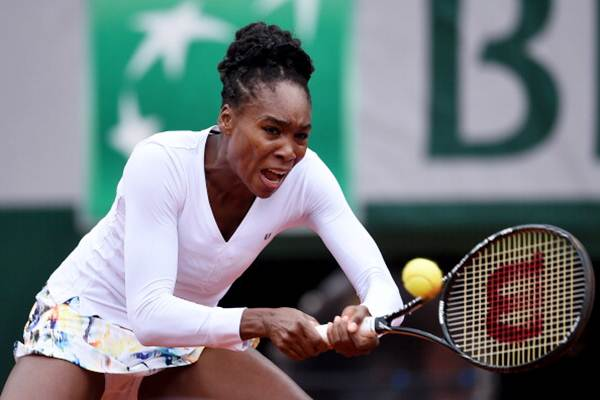 Venus Williams of the United States returns a shot during her women's singles match against Anna Schmiedlova of Slovakia