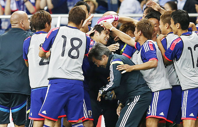 Japan's Atsuto Uchida (centre) celebrates with teammates after scoring against Cyprus during their international friendly in Saitama, Tokyo on Tuesday