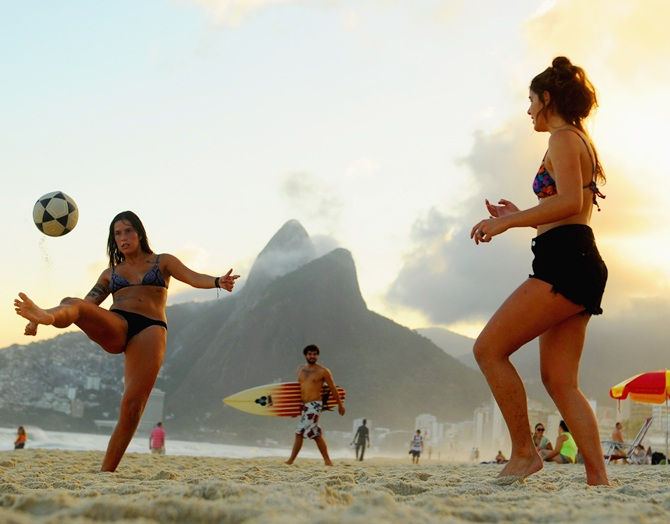 Women play football on Ipanema beach.