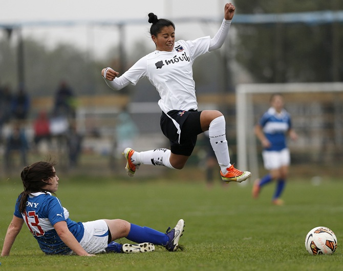 Claudia Soto (top) of Colo Colo women's soccer club jumps of a rival from Universidad Catolica during a match in Santiago.