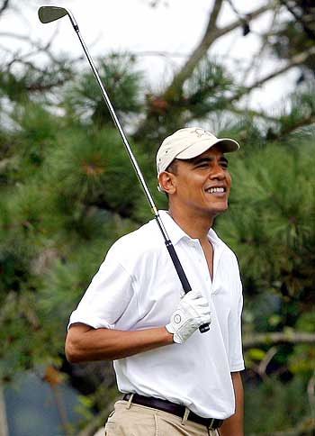 US President Barack Obama watches his tee shot while golfing at Mink Meadows golf course