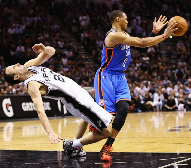 Manu Ginobili of the San Antonio Spurs falls to the court after colliding   with Russell Westbrook of the Oklahoma City Thunder