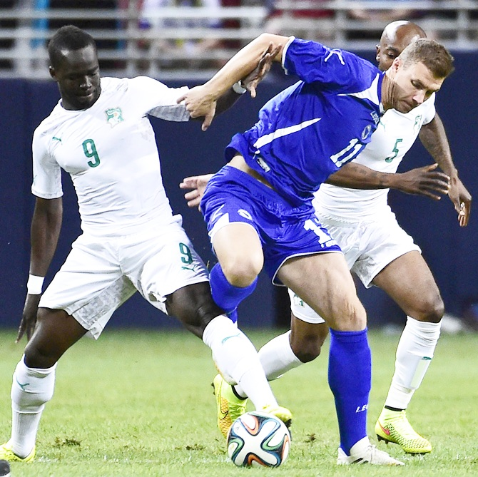 Bosnia player Edin Dzeko, centre, battles for the ball between Ivory Coast players Ismael Tiote Cheik and Didier Zokora