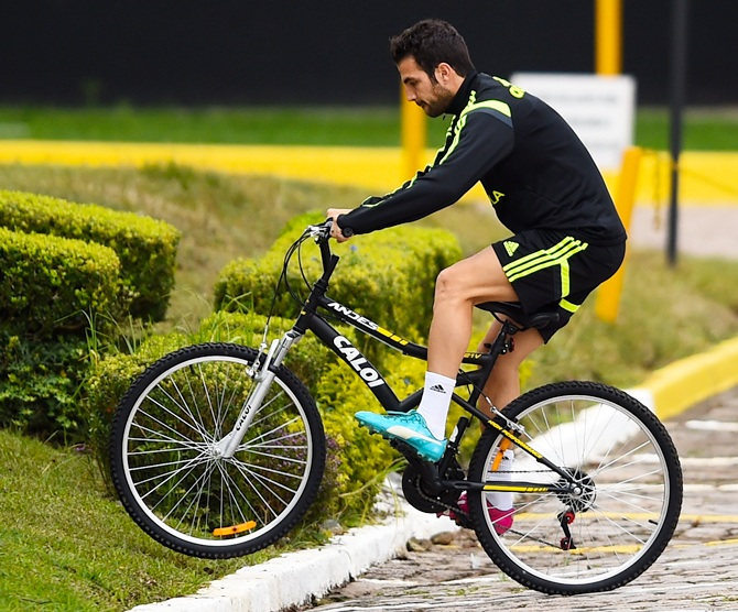 Cesc Fabregas of Spain rides a bicycle