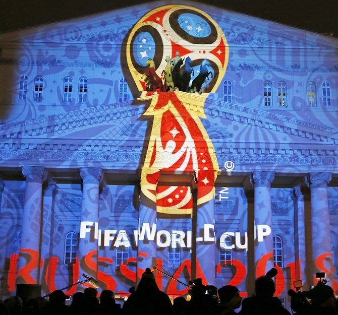 Journalists look at a light installation showing the   official logotype of the 2018 FIFA World Cup