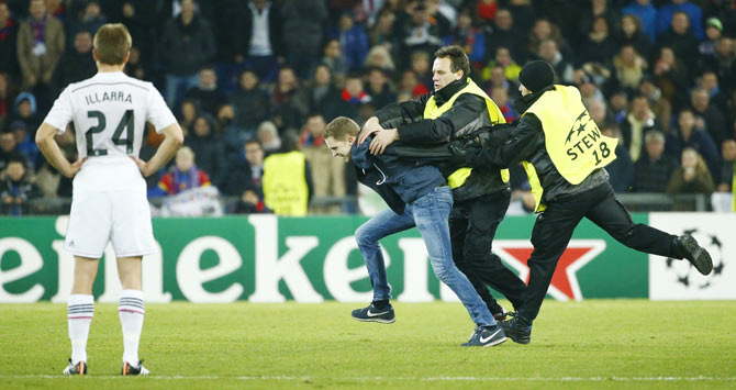 A fan is chased by stewards as he runs on the field during the Champions League Group B soccer match between FC Basel and Real Madrid on Wednesday