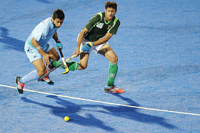 Manpreet Singh of India (left) and a Pakistani player in action during their match on Thursday