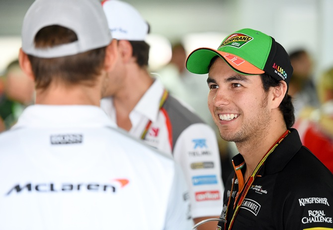 Sergio Perez of Mexico and Force India speaks with Jenson Button