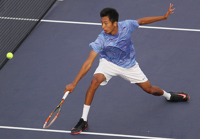 Chuhan Wang of China returns a shot during his match against Fabio Fognini of Italy during the day 3 of the Shanghai Rolex Masters at the Qi Zhong Tennis Center on October 7, 2014 in Shanghai, China