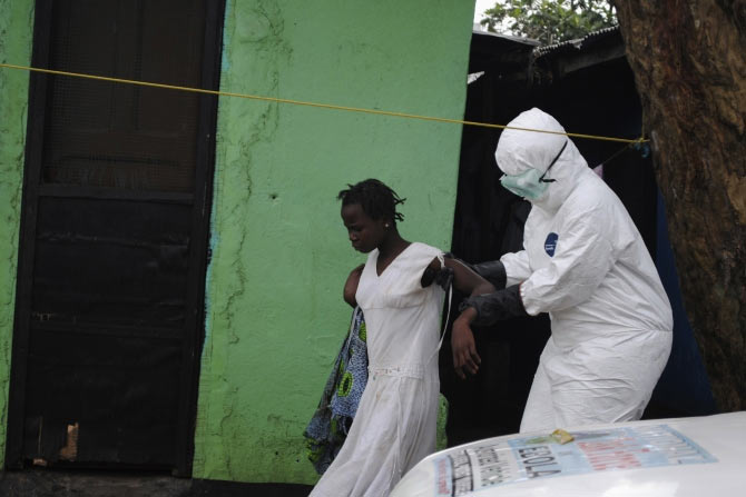 A health worker brings a woman suspected of having contracted the Ebola virus to an ambulance in Monrovia, Liberia