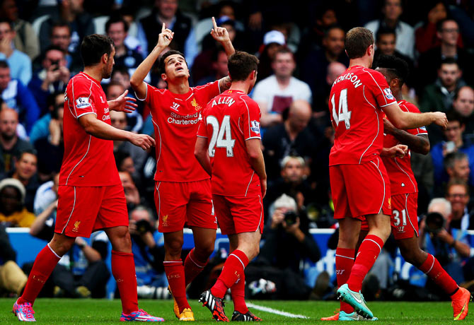 Philippe Coutinho of Liverpool celebrates with teammates after scoring against Queens Park Rangers during their English Premier League match at Loftus Road in London on Sunday