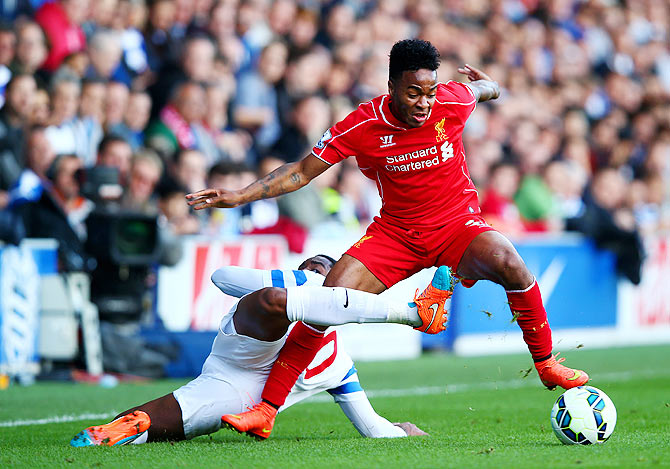 Raheem Sterling of Liverpool (left)battles for the ball with Leroy Fer of QPR