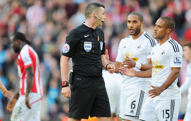 Swansea player Wayne Routledge (right) and Ashley Williams (centre) confront referee Michael Oliver after Stoke City's Victor Moses (left) was awarded a controversial penalty on Sunday