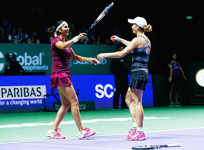 Cara Black of Zimbabwe and Sania Mirza of India celebrate defeating Raquel USA's Kops-Jones and Abigail Spears in the doubles quarter-finals at the WTA Finals on Thursday
