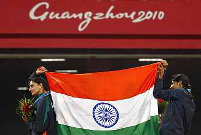 Members of India's women's 4x400m relay team celebrate their win at the 16th Asian Games in Guangzhou