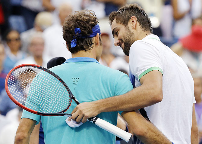 Croatia's Marin Cilic (right) and Roger Federer of Switzerland embrace after the 2014 US Open semi-final