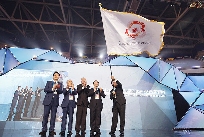 Rejepgeldy Nurmammedow (R), Head of Government of Ashghabat city, Turkmenistan, the next host city of Asian Indoor & Martial Arts Games waves OCA flag