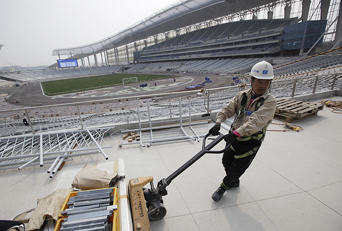 A labourer works at the Incheon Asiad Main Stadium in Incheon