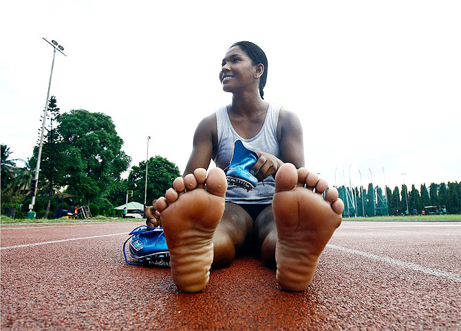 Heptathlete Swapna Barman prepares to wear her track shoes before a practice session at Salt Lake stadium in Kolkata