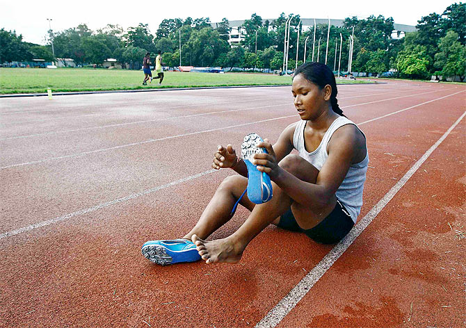 Heptathlete Swapna Barman removes her track shoes after a practice session at Salt Lake stadium in Kolkata