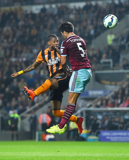 Hull striker Abel Hernandez beats West Ham defender James Tomkins (right) in an aerial challenge to score the first goal at KC Stadium in Hull on Monday