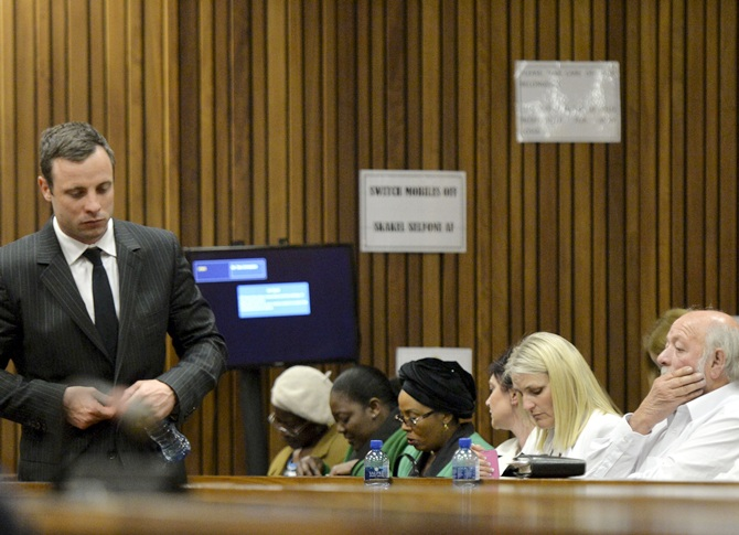 Oscar Pistorius walks past Reeva Steenkamp's parents in the Pretoria High Court
