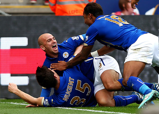 Esteban Cambiasso of Leicester City celebrates with teammates David Nugent and Liam Moore after scoring his team's third goal during the Barclays Premier League match against Manchester United at The King Power Stadium in Leicester on Sunday