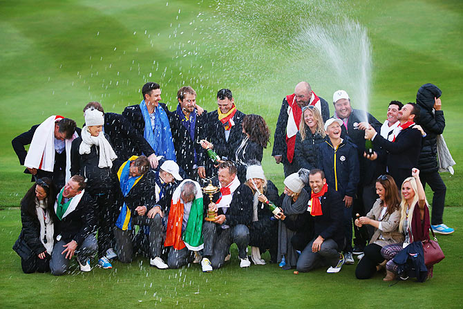 Europe team captain Paul McGinley poses with the Ryder Cup trophy, his team and their partners and wives after the Singles Matches of the 2014 Ryder Cup on the PGA Centenary course at the Gleneagles Hotel in Auchterarder, Scotland, on Sunday