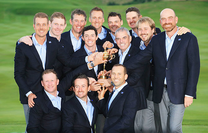Europe team captain Paul McGinley poses with the Ryder Cup trophy and his team after the Singles Matches
