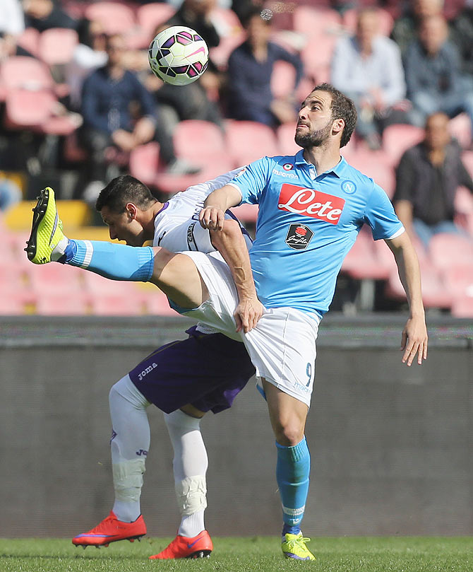 Napoli's Gonzalo Higuain (right) competes for the ball with Fiorentina Manuel Pasqual during their match at Stadio San Paolo in Naples on Sunday